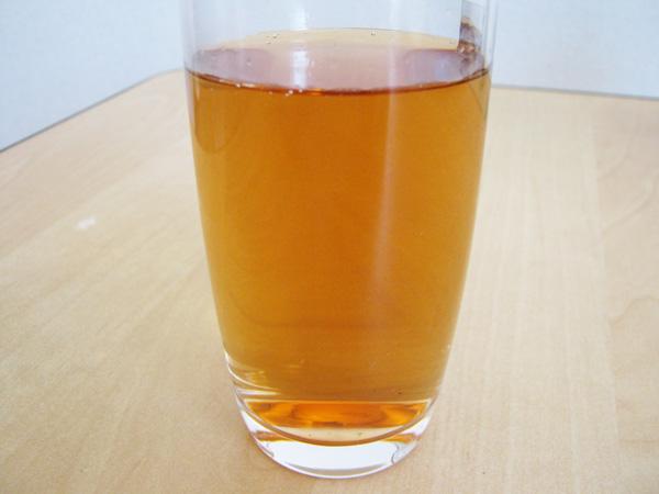 グラスに入った黄金色の柿の葉茶の拡大写真